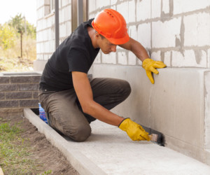 Construction man applying paint on cement